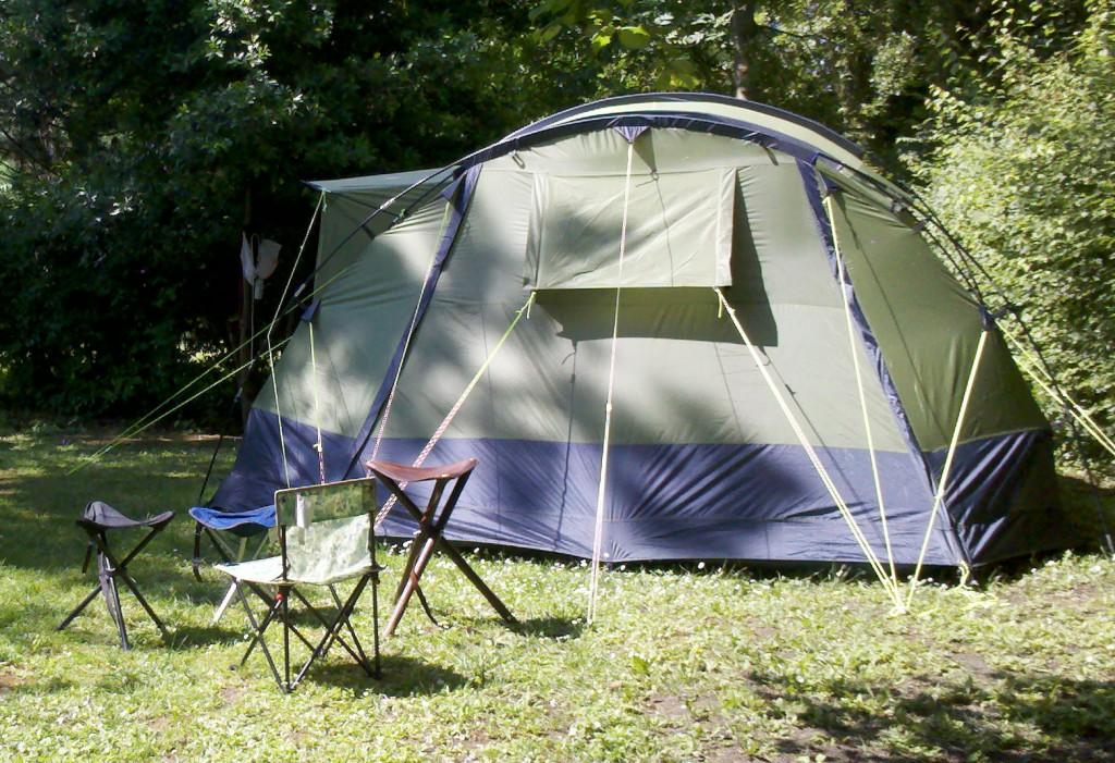 Stirnseite. Das Zelt kann an den beiden vertikalen blauen Streifen geöffnet werden und ist an dieser Stelle nicht mit der Bodenplane verbunden.